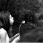 タンポポ吹いてる横顔女性